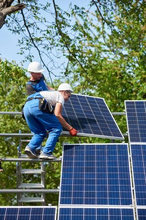 Two workers mounting heavy solar photo voltaic panel on tall steel platform standing on ladder on green tree and blue sky background. Exterior solar system installation, dangerous job concept.
