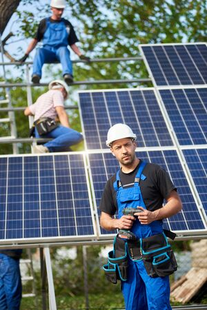Portrait of successful engineer technician with electrical screwdriver standing in front of unfinished high exterior solar panel photo voltaic system, with team of workers on high platform background.