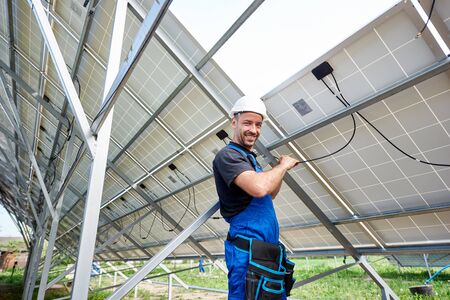 Smiling engineer technician making electrical wiring standing inside high exterior solar panel photo voltaic system on bright sunny summer day. Eco friendly cheap electricity generation concept.