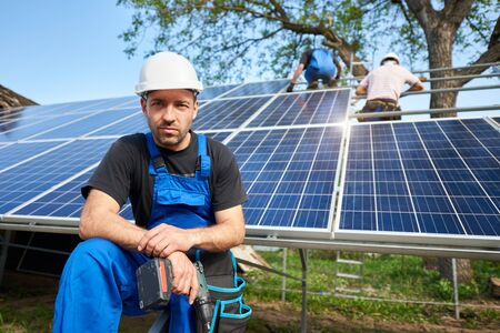 Portrait of successful engineer technician with electrical screwdriver in front of almost finished high exterior solar panel photo voltaic system, with team of workers on high platform. Stok Fotoğraf