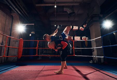 athlete man fighter training mma with his trainer, fighting in the ring at the health club Stok Fotoğraf