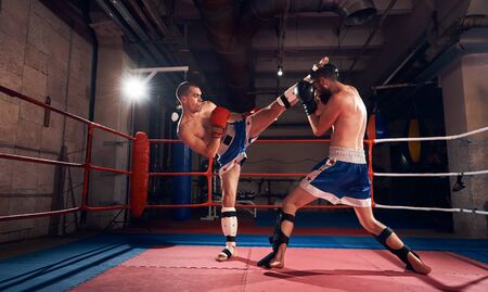 Two athletic sportsmen kickboxers practicing kickboxing in the ring at the sport club Stok Fotoğraf