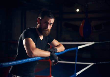 Portrait of young fighter standing in the ring at the health club after hard exercising kickboxing