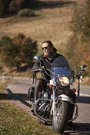 Handsome bearded biker in black leather jacket and sunglasses sitting on cruiser motorcycle on country roadside