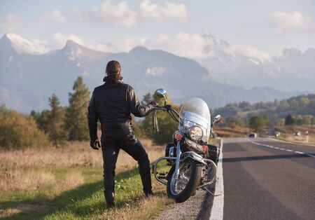 Back view of tall athletic motorcyclist in black leather clothing standing at cruiser powerful motorbike on background of green rural landscape, steep mountain peaks and bright sky.