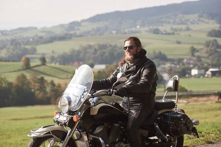 Side view of handsome bearded motorcyclist with long hair in black leather jacket and sunglasses, sitting on modern motorcycle on blurred background of green peaceful rural landscape.