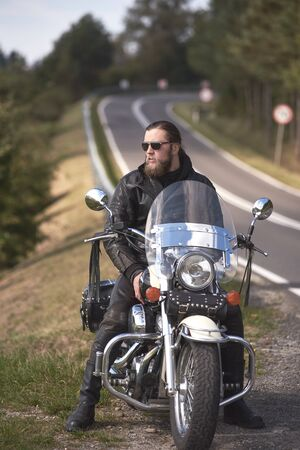 Handsome bearded biker with long hair in leather jacket and sunglasses sitting on cruiser motorcycle on roadside, on blurred background of empty twisty road with white marking on sunny summer day.