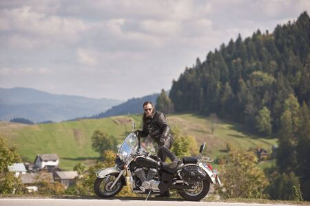 Side view of handsome bearded biker in black leather jacket and sunglasses sitting on cruiser motorcycle on roadside on blurred background of foggy spruce forest, green hills and bright cloudy sky. Stok Fotoğraf