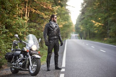 Young bearded tall athletic motorcyclist in black leather outfit and dark sunglasses standing at shiny modern powerful motorbike, on blurred background of hilly asphalt road and green trees. Stok Fotoğraf