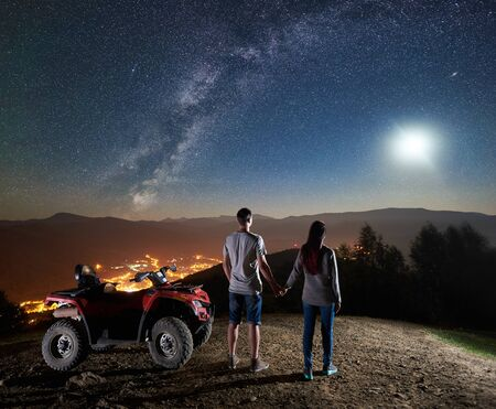 Back view of young couple tourists with atv quad motorbike on the top of mountain. Man and woman holding hands, enjoying night sky full of stars, full moon, Milky way, luminous city on background