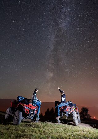 Happy romantic couple man and woman tourists with atv quad motorbikes on the top of mountain. Man pointing at beautiful night sky full of stars and Milky way Stok Fotoğraf