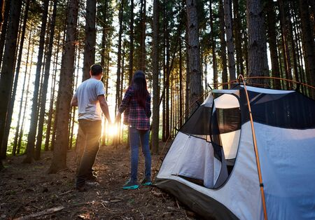 Back view of man and woman travellers holding hands, standing near white tourist tent. Romantic couple enjoying beautiful view of setting sun. Evening camping at sunset in the forest.
