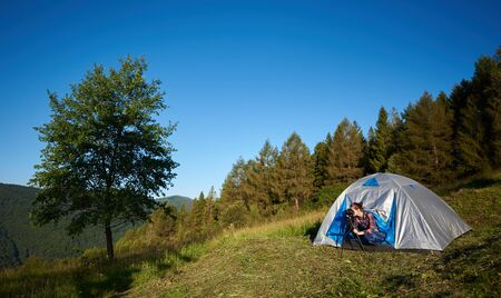 Summer morning camping in the mountains. Young woman hiker sitting in tourist tent, taking photo, using photo camera and tripod. On background blue sky, forest and big tree.