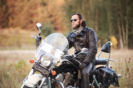 Handsome bearded motorcyclist in black leather clothing and dark sunglasses sitting on black shiny cruiser bike, on blurred vintage sunny bokeh background of golden-green trees foliage in the evening.