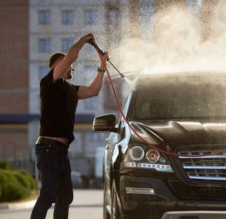 Side view of a stylish man cleaning his black car outdoors, water is splashing over the top of the car shining on the sun, residential building is on the background