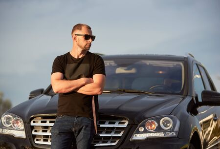 Portrait of a successful self-confident man standing in front of his black car with crossed hands, looking away, wearing dark sunglasses, black t-shirt and jeans, close-up, copy space