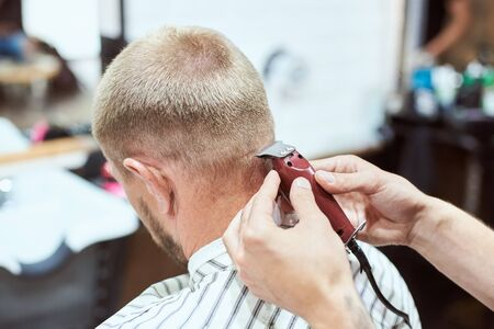 Dark blonde man at barber shop is having his nape shaved with a trimmer, hairdresser is holding a red tool, stripe cape on Stock Photo