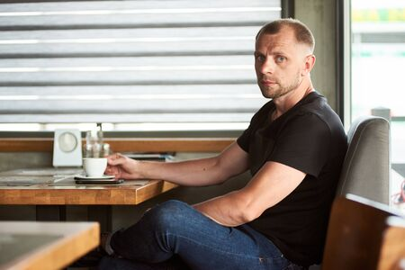 Handsome thoughtful sporty man is holding a cup of coffee, sitting at the window side table in cafe, looking at the camera, wearing black t-shirt and dark blue jeans