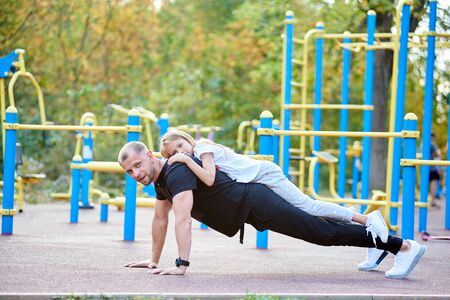 Father is doing push ups on the ground outdoors with his daughter on his back, looking in the camera, healthy lifestyle with family, workout, side view Stok Fotoğraf