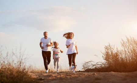 Front view of young and beautiful family of three jogging with their dog outside the city on the village road on the setting sun Stok Fotoğraf