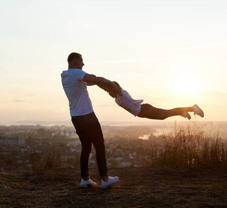 Silhouette of a father swinging his daughter by the arms on the hill on the setting sun in the suburbs, beautiful horizon on the background, side view