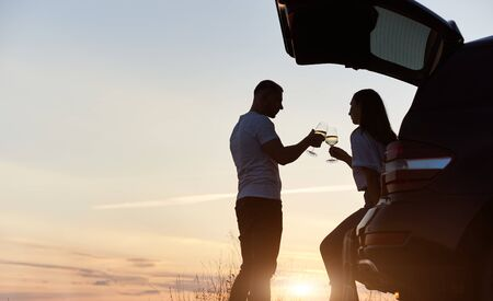 Beautiful silhouette of a couple, husband and wife, having romantic time drinking wine in the car trunk on the hill on the sunset, evening sky on the background, copy space