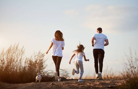 Back view of sporty family - father, mother and daughter are jogging with their jack russell terrier outside the city on the village road at the sunset Archivio Fotografico - 137435439