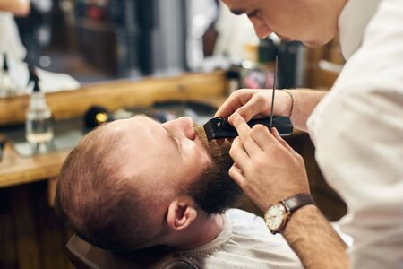 Using of electric trimmer machine for styling mustaches and beard. Accuracy and concentration of professional barber. Work process in modern hairdressing salon for men. Cropped close up view.
