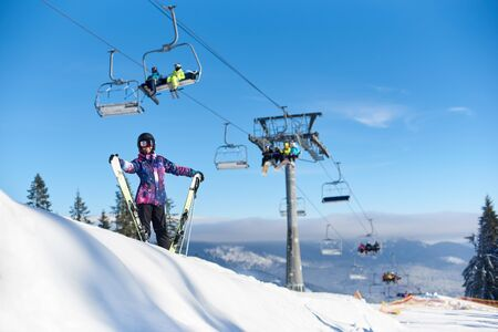 Happy woman in goggles and helmet with her skis standing near ski lift on snow-covered mountain slope. Female going spending time out skiing. Ski lift in action. Sunny day during winter vacation.