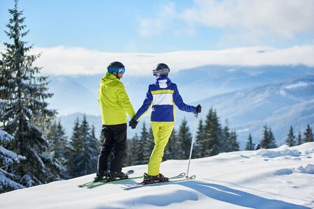 Back view of couple of skiers on mountain edge holding hands, looking to each other. Winter mountain panoramic landscape on blurred background. Romantic, love, family, vacation, ski resort concept.