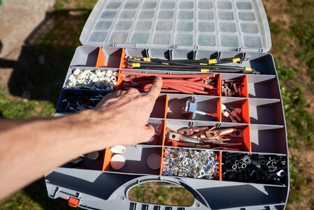 Photo of worker's hand choosing detail from big opened case needing by exterior technology solar battery mounting Modern solution for natural resources saving, using renewable solar energy.