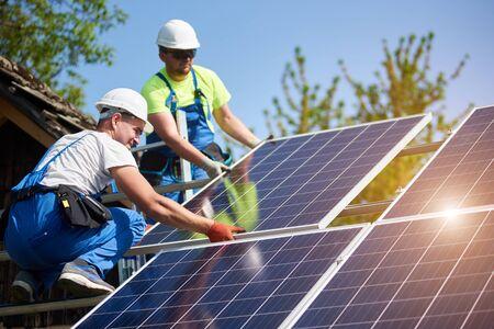 Twee professionele technici installeren zware fotovoltaïsche zonnepanelen op een hoog stalen platform. Exterieurinstallatie van het zonnestelsel, alternatief concept voor de opwekking van groene energie.