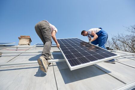 Male engineers installing solar photovoltaic panel system. Electricians lifting blue solar module on roof of modern house. Alternative energy sustainable concept.
