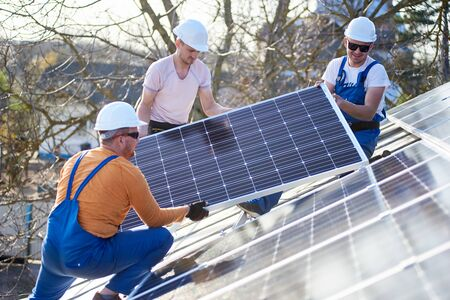 Male engineers installing stand-alone solar photovoltaic panel system. Electricians mounting blue solar module on roof of modern house. Alternative energy ecological concept.