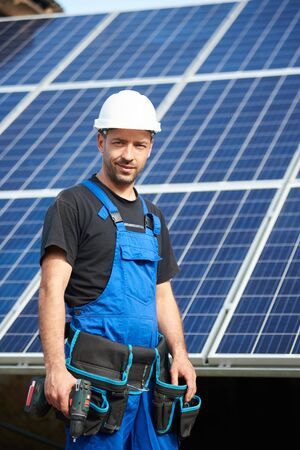 Portrait of happy engineer technician in white protective helmet and blue overalls with electrical screwdriver on background of exterior solar panel photo voltaic system blue shiny surface. Foto de archivo - 137435677