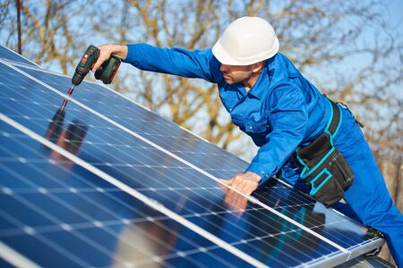 Man worker in blue suit and protective helmet installing solar photovoltaic panel system using screwdriver. Electrician mounting module on roof of modern house. Alternative energy ecological concept.