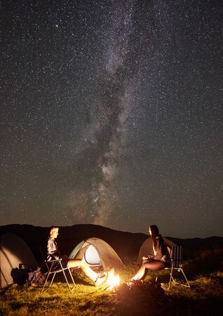 Happy couple hikers relaxing at summer night camping in the mountains. Young man and woman sitting on chairs beside campfire and tourist tents under beautiful starry sky full of stars and Milky way. Foto de archivo - 137435678