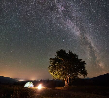 Tourist camping near big tree at night in the mountains. Glowing tent and bonfire under amazing night sky full of stars and Milky way. Tourism adventure active lifestyle astrophotography concept Foto de archivo - 137435679