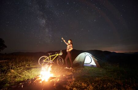 Young woman cyclist enjoying at night camping, pointing at evening sky full of stars and Milky way, standing near campfire, illuminated tourist tent, mountain bike. Outdoor activity concept Foto de archivo - 137435686