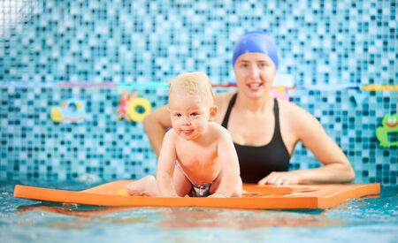Small child spending fun time in swimming pool. Cute little boy is crawling on a floating mat, mother is behind him supporting. Concept of active leisure Foto de archivo - 137436523