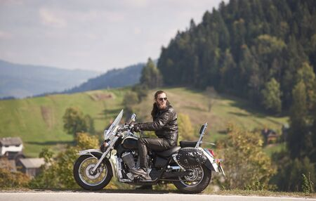 Side view of handsome bearded biker in black leather jacket and sunglasses sitting on modern motorcycle on roadside on blurred background of foggy spruce forest, green hills and bright sky. Foto de archivo - 137436575