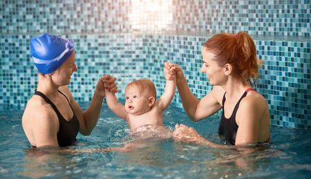Two women holding a baby boy hands up in swimming pool on blue background. Safety swim activities for infants Foto de archivo - 137436590