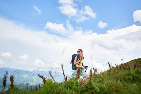 Attractive woman hiker hiking in Carpathian mountain trail, walking on grassy hill, wearing backpack and sunglasses, using trekking sticks, enjoying summer day. Outdoor activity, lifestyle concept Foto de archivo - 137436589