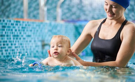 Young smiling mother is helping her little son swim in turquoise water during swimming class for infants, baby is splashing around in water. Concept of active family leisure 版權商用圖片