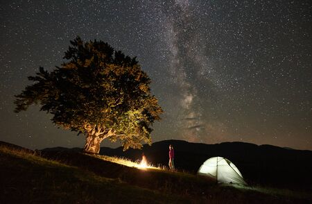 Female camper resting at summer night camping in the mountains beside bonfire, illuminated tourist tent and big tree. Young woman traveller enjoying view of night sky full of stars and Milky way. Foto de archivo - 137436595