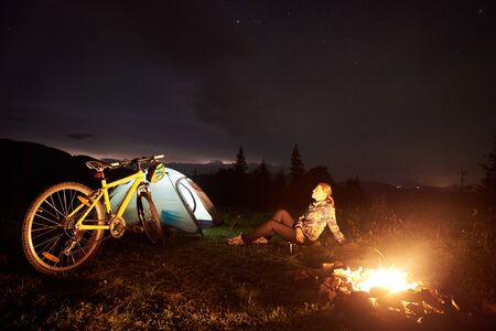 Young woman cyclist having a rest at night camping near burning campfire, illuminated tourist tent, mountain bike under beautiful evening sky full of stars. Outdoor activity and tourism concept Foto de archivo - 137436596