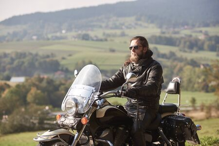 Handsome bearded rider with long hair in black leather jacket and sunglasses sitting on cruiser motorcycle, on blurred background of green peaceful rural landscape and light foggy sky. Foto de archivo - 137436597