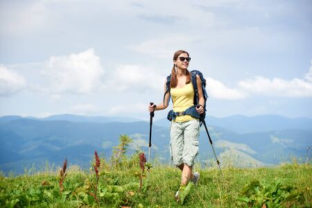 Athlete happy woman backpacker hiking mountain trail, walking on grassy hill, wearing backpack and sunglasses, using trekking sticks, enjoying summer cloudy day. Outdoor activity, tourism concept Foto de archivo - 137436598