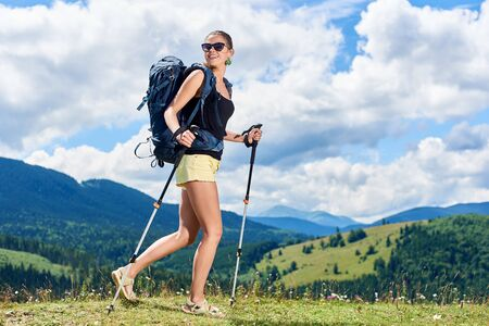 Slim happy woman hiker hiking mountain trail, walking on grassy hill, wearing backpack and sunglasses, using trekking sticks, enjoying summer sunny day in the mountains. Tourism concept