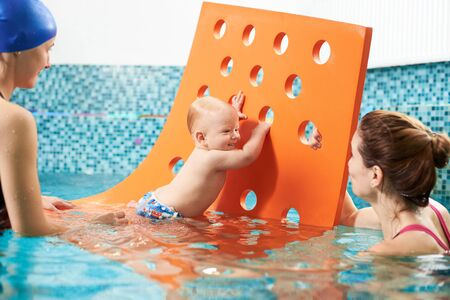 Interactive swimming training class with additional protective tools for infants. Little baby boy is using a floating mat with holes to get on his feet, mother and instructor is helping him Foto de archivo - 137436600